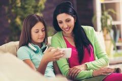 La madre feliz y su hija adolescente linda están mirando el teléfono móvil Foto de archivo