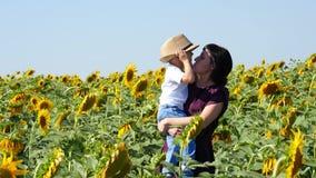 La madre feliz y su hijo en un girasol colocan en la puesta del sol Una mujer joven detiene a un bebé en sus brazos metrajes