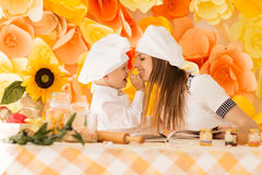 La madre feliz y su niño bajo la forma de cocineros preparan un festiv Imágenes de archivo libres de regalías