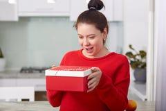 La madre futura felice riceve il contenitore di regalo dall'amico, apre il presente con la gioia e la sorpresa, ha compleanno, pa immagine stock