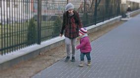 La madre gioca con sua figlia, sia corrente lungo il recinto Il concetto della famiglia Movimento lento stock footage