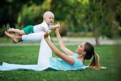 La madre graziosa allegra sta facendo l'allenamento su prato inglese con il piccolo figlio Mette in mostra il concetto, ora legal Fotografie Stock Libere da Diritti
