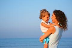 La madre guarda al niño en las manos del borde del mar Fotos de archivo libres de regalías