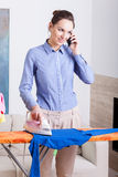 La madre habla en el teléfono mientras que plancha Imagen de archivo libre de regalías
