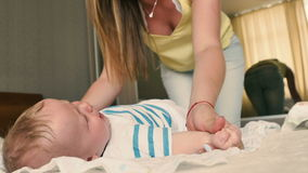 La madre hace deportes los ejercicios con el bebé de mentira en la cama metrajes