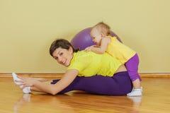 La madre hace ejercicios físicos con su hija Fotos de archivo