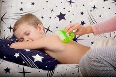 La madre hace el masaje de la parte posterior de su pequeño hijo Fotos de archivo libres de regalías