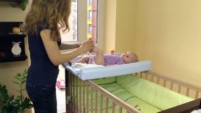 La madre hace el masaje terapéutico del pie para el bebé en tablero de la envoltura metrajes