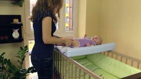 La madre hace el masaje terapéutico para la mentira del niño en tablero de la envoltura almacen de metraje de vídeo