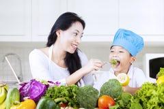 Muchacho feliz que come el bróculi con la mamá en casa Foto de archivo libre de regalías