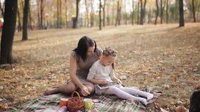 La madre hermosa joven con su hija escribe en tiza en un tablero de tiza en el parque del otoño almacen de metraje de vídeo