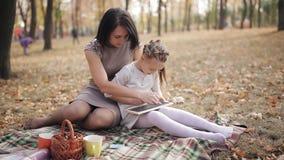 La madre hermosa joven con su hija escribe en tiza en un tablero de tiza en el parque del otoño almacen de video