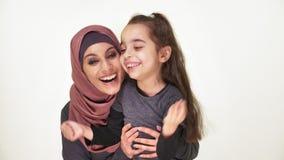 La madre hermosa joven en hijab abraza a su pequeña hija, familia de risa, concepto de familia feliz, idilio, mirada en la cámara metrajes