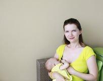 La madre hermosa joven está amamantando al bebé. Tiempo del oficio de enfermera en el th imagenes de archivo
