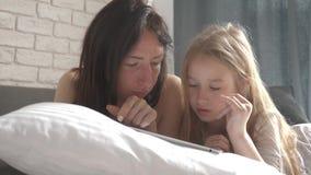 La madre hermosa joven y su hija linda hace compras en línea en una tableta y la sonrisa mientras que miente en la cama en almacen de video