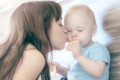 La madre hermosa que juega con su niño hermoso, el niño come la galleta y las risas imagen de archivo libre de regalías