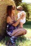 La madre hermosa y el bebé jovenes que abrazan en un prado florece Foto de archivo libre de regalías