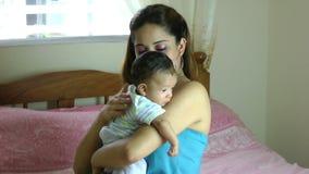 La madre hispánica de Latina que celebra al bebé que babea sobre hombro y que golpea ligeramente en la parte posterior así que el almacen de metraje de vídeo