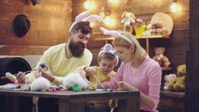 La madre, il padre ed il figlio stanno dipingendo le uova La famiglia felice sta preparando per Pasqua Coniglietto d'uso del raga archivi video