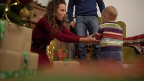 La madre, il papà ed il bambino allegri allegri svegli passano il loro tempo libero accanto all'albero di Natale a casa stock footage