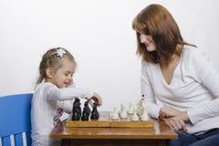 La madre insegna alla figlia a giocare gli scacchi fotografie stock