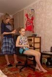 La madre intreccia i suoi capelli nella figlia di 14 anni della treccia fotografia stock