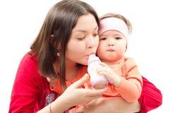 La madre introduce a su pequeña hija con una botella Foto de archivo