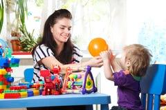 La madre invia i piccoli bambini dei palloni Fotografia Stock