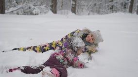La madre joven admira a su bebé que se divierte que juega en la nieve La niña pasa activamente tiempo en el invierno almacen de video