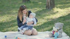 La madre joven alimenta a su pequeño hijo en la sobrecama en parque metrajes