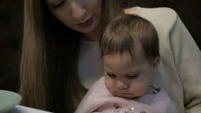 La madre joven alimenta a una niña con un queso de Suluguni almacen de video
