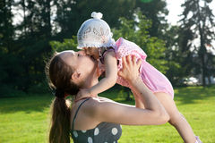 La madre joven besa a su hija imagenes de archivo