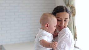 La madre joven calma a un pequeño bebé gritador en casa en el dormitorio Primer almacen de video
