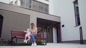 La madre joven camina con su hija de la niña alrededor de la casa que se sienta en hablar del banco almacen de metraje de vídeo