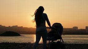 La madre joven camina con un niño que se sienta en un carro de bebé en el río en la puesta del sol metrajes