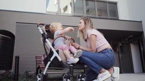 la madre joven camina con una niña con su hija en un carro de bebé cerca de la casa metrajes