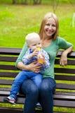 La madre joven celebra en las manos de su hijo de dos años Imagenes de archivo
