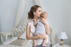 La madre joven celebra en las manos a su pequeño bebé en casa (la visión trasera) Imagen de archivo