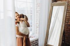 La madre joven celebra en sus manos a su pequeña hija después la ventana y el espejo en el cuarto acogedor ligero fotos de archivo