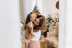 La madre joven celebra en sus manos a su pequeña hija en el cuarto acogedor con el árbol del Año Nuevo fotos de archivo