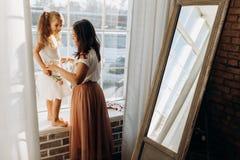La madre joven celebra su pequeña situación de la hija en el alféizar al lado del espejo en el lleno de sitio acogedor ligero fotos de archivo