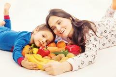 La madre joven come la fruta y verdura con su hijo joven imagenes de archivo