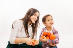 La madre joven come la fruta y verdura con su hijo joven foto de archivo libre de regalías