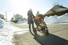La madre joven con el bebé en cochecito camina invierno de la calle Imagen de archivo