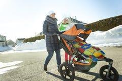 La madre joven con el bebé en cochecito camina invierno de la calle Foto de archivo libre de regalías