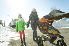 La madre joven con el bebé en cochecito camina invierno de la calle Foto de archivo