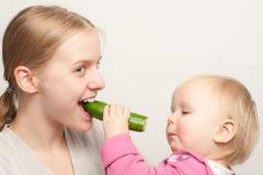 La madre joven con la hija del niño come cumber Imagen de archivo libre de regalías