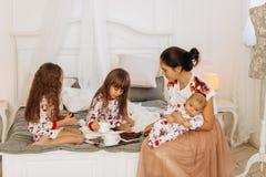 La madre joven con su bebé minúsculo sienta o la cama con sus dos hijas vestidas en pijamas que come las galletas con cacao con foto de archivo libre de regalías