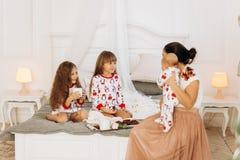 La madre joven con su bebé minúsculo sienta o la cama con sus dos hijas vestidas en pijamas que come las galletas con cacao con fotografía de archivo libre de regalías