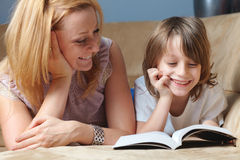 La madre joven con su hijo leyó el libro en el sofá Foto de archivo